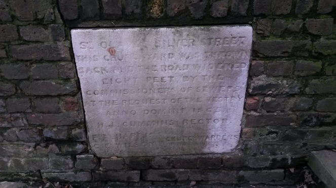 Close up image of the plaque described in the previous paragraph.  It is made of a pale stone, and is set within a wall made of dark-coloured bricks..