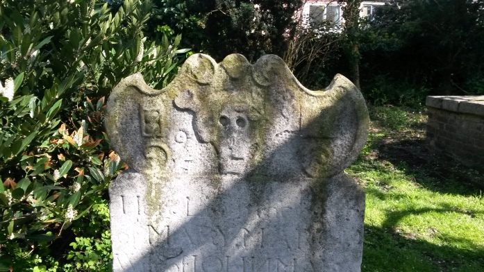 This headstone from 1752 has both the death head and hourglass symbols on it.