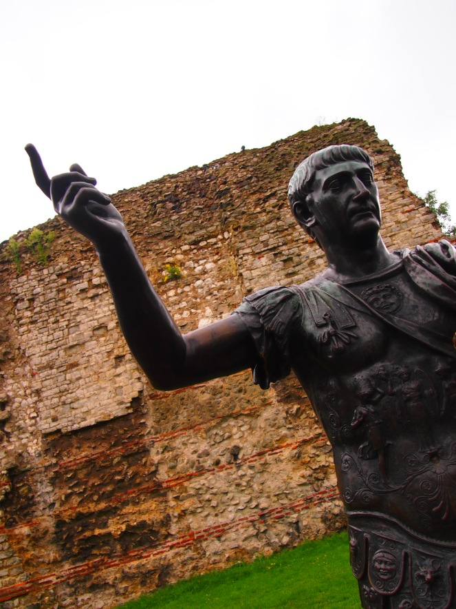 A statue of thte Emperor Trajan is located by remains of the Roman city walls near the Tower of London