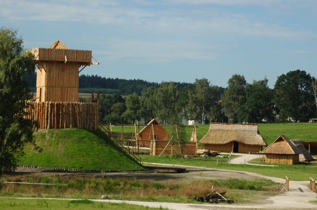 A reconstructed motte with wooden keep (image via Barbara Brunner on Wikimedia Commons)