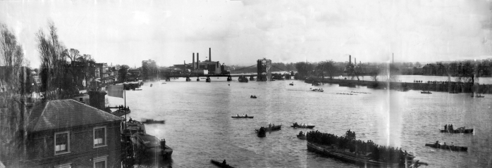 Photograph of the University Boat Race in 1886, with Hammersmith Bridge under construction. (click on the image to enlarge) Image via Wikimedia Commons.