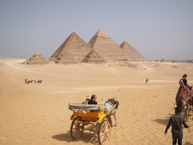 Image showing the Pyramids of Giza, with a horse-drawn carriage and camels in the foreground