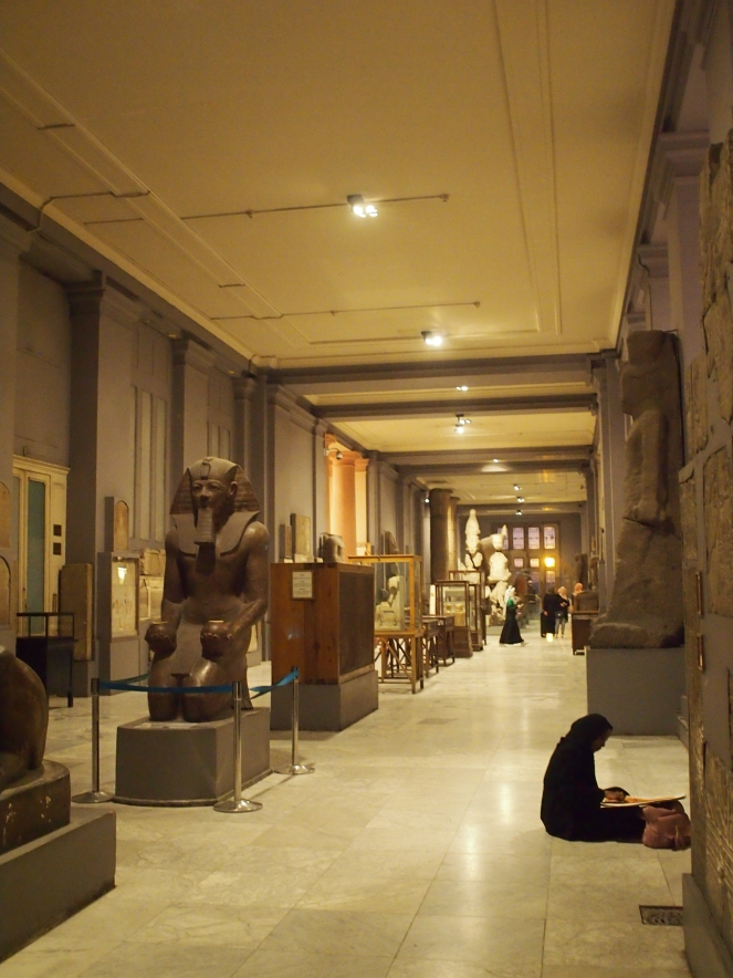 Photograph showing the interior of the museum; a long gallery with statues and glass cases