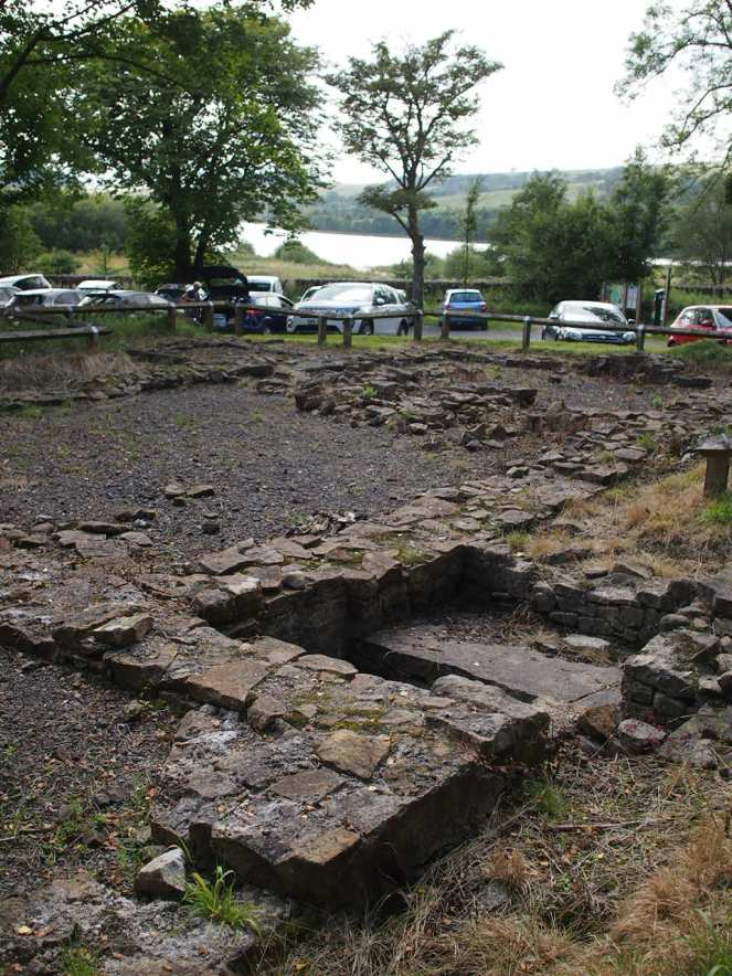 Picture shows the foundations of the original church; in the background is a car park and the Stocks Reservoir